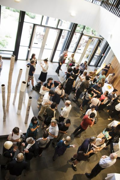 Image from above of people gathered in a foyer talking