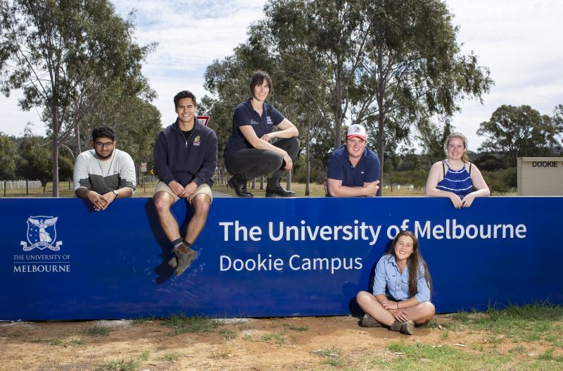 Students sitting in front of the Dookie College sign at the University of Melbourne's Dookie campus