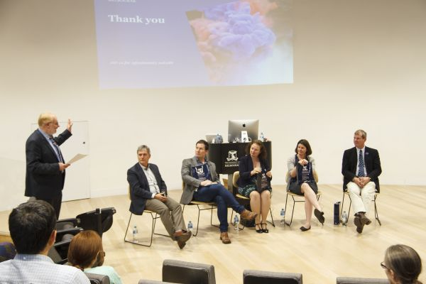 The conclusion of the panel. One person standing and speaking, with five panel members sitting in a line