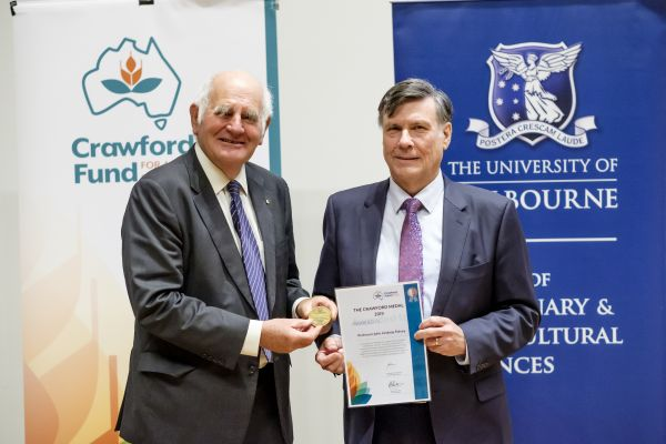 Dr Tony Gregson (left) presents Professor Lindsay Falvey with the 2019 Crawford medal.